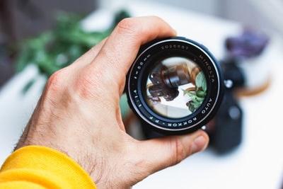カメラのレンズを持つ画像