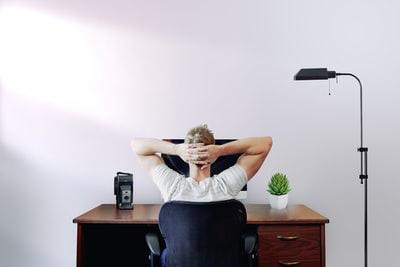 机の椅子に寄っかかっている図