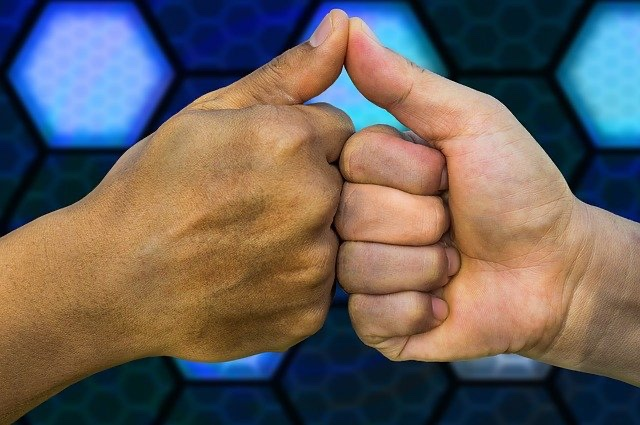 拳と拳を合わせている画像
